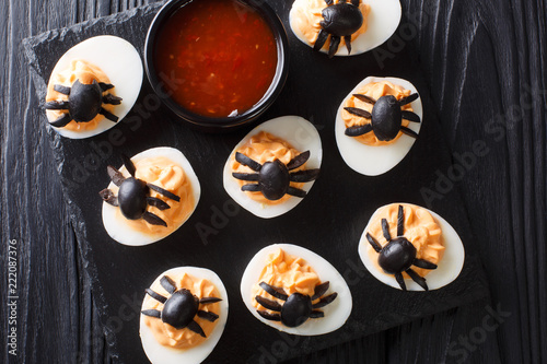 Halloween appetizer deviled eggs stuffed with mustard and decorated with olive spiders and cobweb close-up. horizontal top view