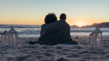 Couple Admiring The Sunset From Beach