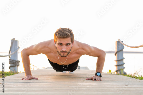 Fotografía  Picture of a young athletic man doing push ups outdoors