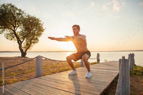 Fotografía Fitness man training air squat exercise on beach outside