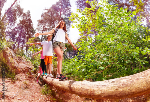 Obraz Boys and girls walk on the big log in forest - fototapety do salonu