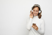 Beautyful Young Woman With Headphones Looks Down At Phone