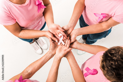 Fotografering  cropped shot of women in pink t-shirts holding breast cancer awareness ribbon is