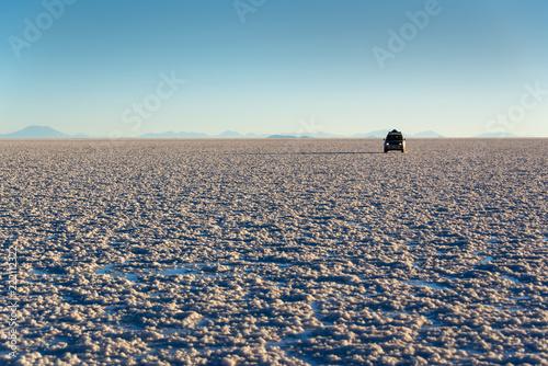 Poster Centraal-Amerika Landen Silhouette of a car in Salar de Uyuni (Uyuni salt flats) at sunset, Potosi, Bolivia