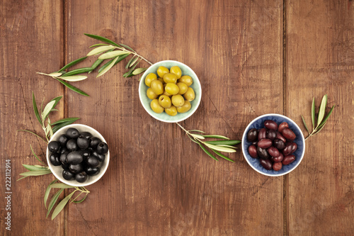 Overhead photo of various olives in bowls with copy space