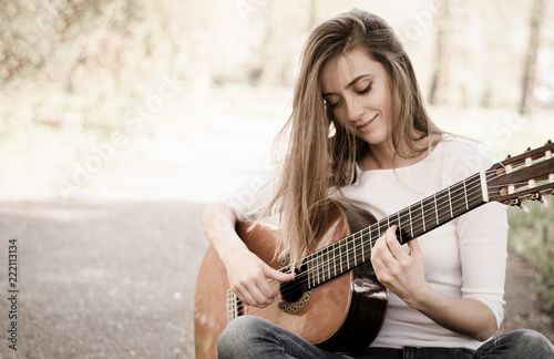 Leinwand Poster Beautiful young girl playing guitar in park. Vintage.