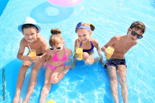 Obraz Cute children with glasses of juice in swimming pool on summer day - fototapety do salonu