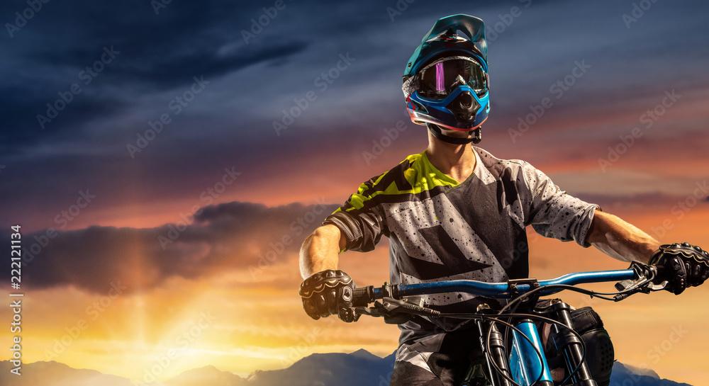 Fototapeta Mountain biker on sunset trail. Male cyclist portrait in sport helmet