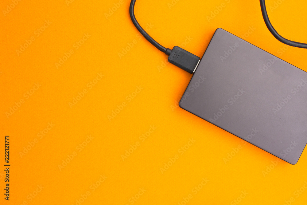 Fototapety, obrazy: Black external hard disk with USB cable on orange background. Top view.