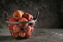 Basket With Fresh Peaches On Grunge Table