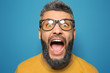 Portrait of screaming man with dyed hair and beard on color background