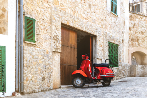vintage red motor scooter parked on cobbled street in hostoric spanish village