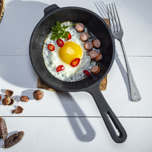 black round frying pan with fried chicken egg and sausages