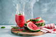Glasses with fresh smoothie and watermelon slices on wooden board