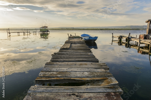 Wooden pier on a lake with a fishing hut. sunset with calm water.