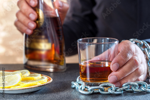 Fotografie, Obraz  Hand of male chained to glass of alcohol drink
