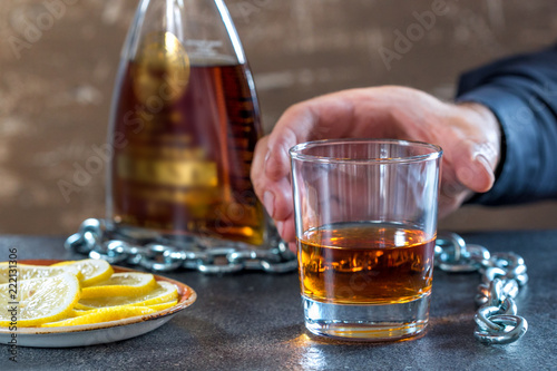 Fotografía  Hand of male chained to glass of alcohol drink