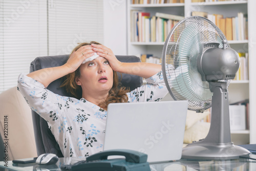 Woman suffers from heat in the office or at home Fototapete