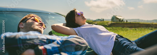Obraz Young couple resting lying on the windshield and the hood of the car - fototapety do salonu