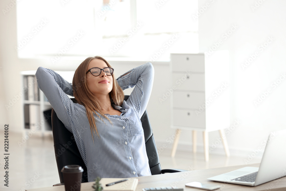 Fototapeta Young businesswoman relaxing at workplace in office