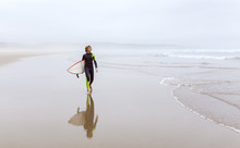 Spain, Aviles, Young Surfer Carrying Surfboard On The Beach