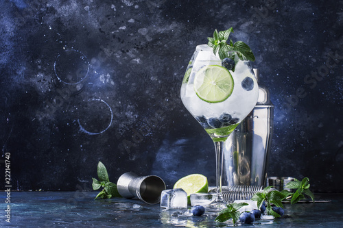 Foto op Plexiglas Cocktail Summer alcoholic cocktail blueberry mojito with rum, green mint, lime and crushed ice, bar tools, gray bar counter, selective focus