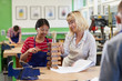 Teacher Helping Female High School Student Building Lamp In Woodwork Lesson