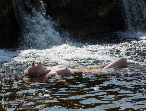 Valokuva  Beautiful young nude woman enjoying summertime in waterfall.
