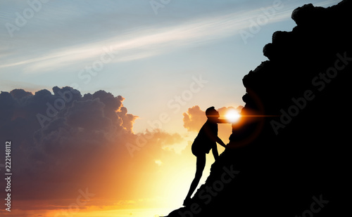 A silhouette of man climbing on mountain top over sunset background, Business, success, leadership, achievement, attempt, patient, endeavor and people concept Canvas Print