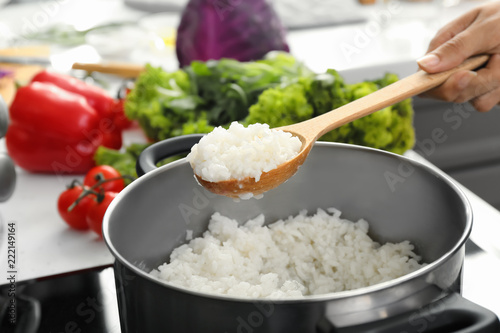 Woman cooking rice in kitchen, closeup Fototapeta