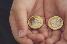 Kid Hand Showing Money Two Pound Coins On His Hands.Child Holding New British One Pound On Both Hands, New Pound Coin, 2017 Design