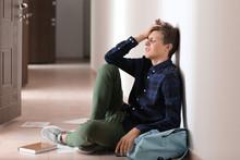 Sad Teenage Boy Sitting On Floor Indoors. Bullying At School