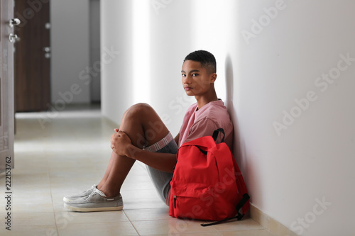 Sad African-American teenage boy sitting on floor indoors Canvas-taulu