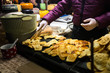 Theme is traditional street food in a European city on the market square in the Czech Republic Prague in the New Year's Eve, Christmas Eve festivities. Hands sell, prepare smoked cheese.