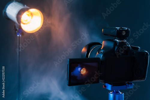 Photo of the camera on a blue tripod that photographs in the studio a professional lighting device in the smoke Canvas Print