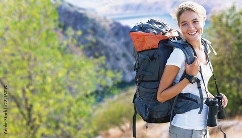 Fototapeta Woman with backpack trekking through the wilderness obraz