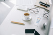 high angle view of cup of coffee and glasses on table in light modern office