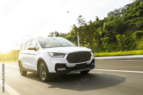 Fototapeta White suv sedan flying fast on the highway obraz