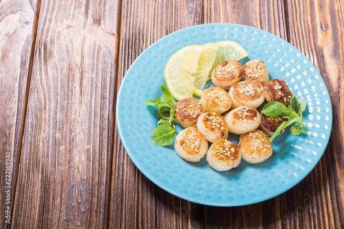 Fried scallops with lemon and salad