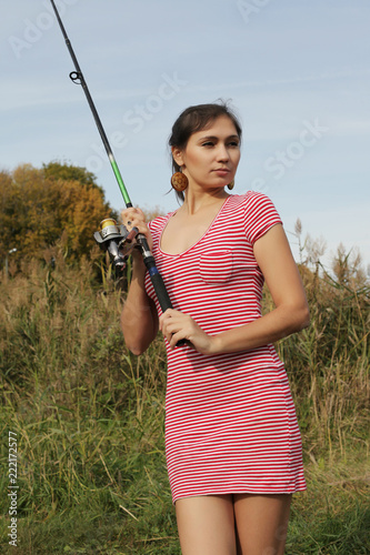 Fotografia  Stunning young girl in a red dress on a fishing trip