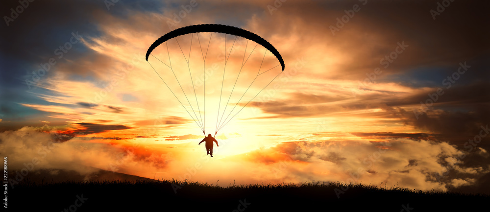 Fototapeta Paragliding in clouds at sunset.