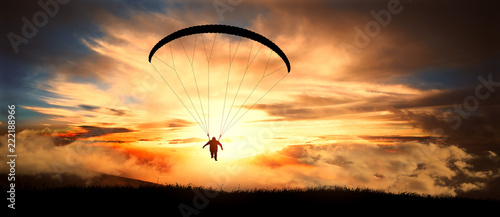 Photo sur Toile Aerien Paragliding in clouds at sunset.