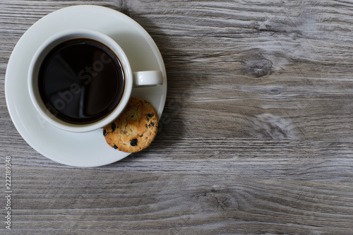 Photo  A cup of hot coffee on a saucer with a chocolate cookie