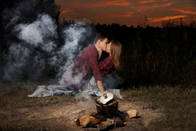Young Couple Kissing While Sitting On The Lake Shore Near The Fire Late In The Evening.