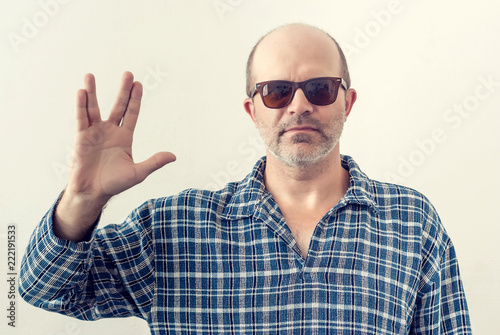 Fotografia, Obraz Portrait of an adult man with a gray beard, dark glasses shirt showing a gesture
