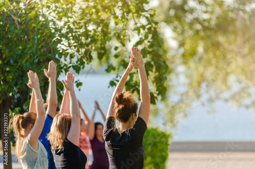 Obraz Group of young people practicing yoga outside in park - fototapety do salonu