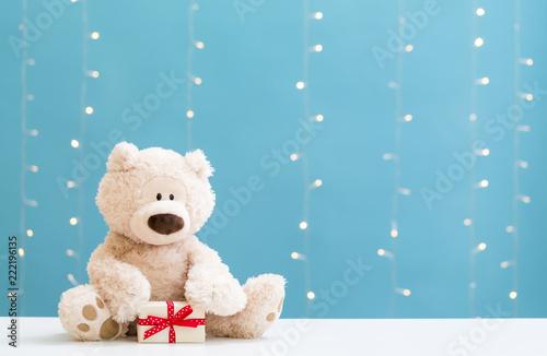 Fotografie, Obraz  A teddy bear and gift box on a shiny light blue background