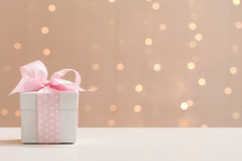 A Gift Box On A Shiny Light Ba...