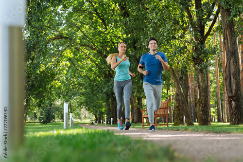 Staande foto Jogging Sport culture. Happy fit couple doing cardio activities while jogging together in the park