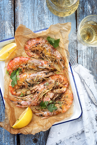 Traditional fried black tiger prawn with lemon and white wine as top view in a white casserole on a wooden blue board